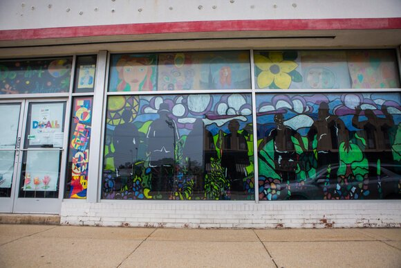 Colorful silhouettes adorn the glass on the front of the Do-Art studio in downtown Bay City.