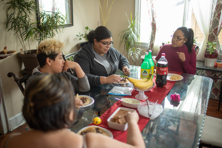 Julissa Robledo (on right) connects with Eleanor Moreno, Angel Robledo-Jimenez, and Maria Moreno-Reyes over a home-cooked meal.