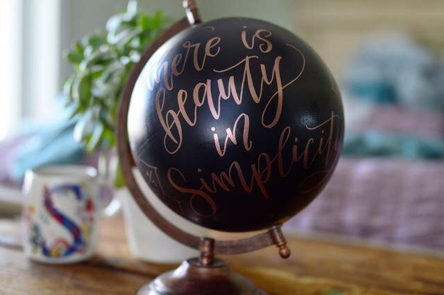 Selena Ashley, a graphic designer and hand-lettering artist, embellishes globes with inspirational sayings.