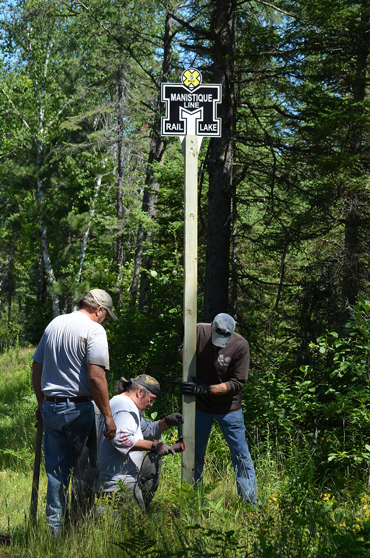 Volunteers installing mile markers with the historic Manistique Line logo (which used to operate on the corridor). On the Haywire Trail in the UP, Michigan's oldest rail trail. Credit: Dan Spegel