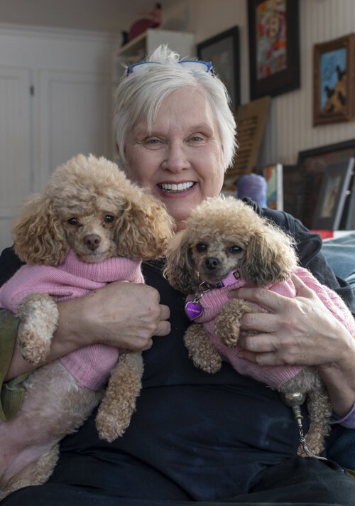 Sue Bergeson, who has discovered a new passion through Mid Michigan College's lifelong learning program, sits in her living room holding her two dogs, Andromeda and Alsyon.