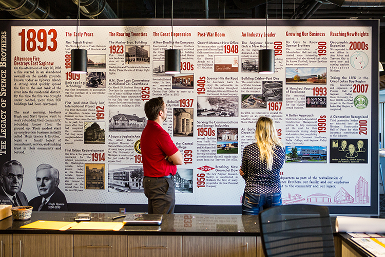Spence Brothers Project Development Lead Wayne Hofmann and Route writer Chelsea Rowley look through the company's history at their headquarters in Saginaw