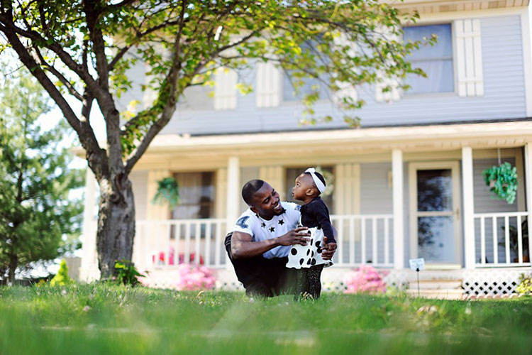 Otis Ebulela plays with his 17-month-old niece, Rebecca, in front of his Delta Township home-Photo Jena McShane