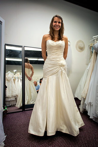 b337ac1ea48 ... Kristen Oltersdorf trying on a dress at The Brides Project Boutique