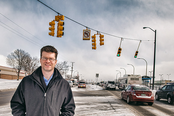 Nathan Voght of ReImagine Washtenaw in the middle of Washtenaw Avenue near Arborland