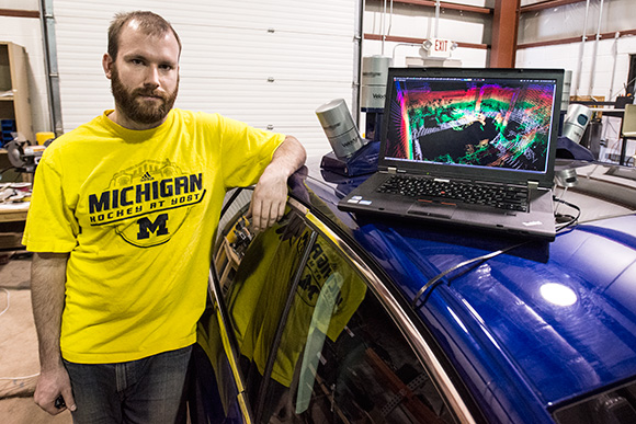 Schuyler Cohen with a Ford Fusion Hybrid Automated Next Generation Vehicle at U of M