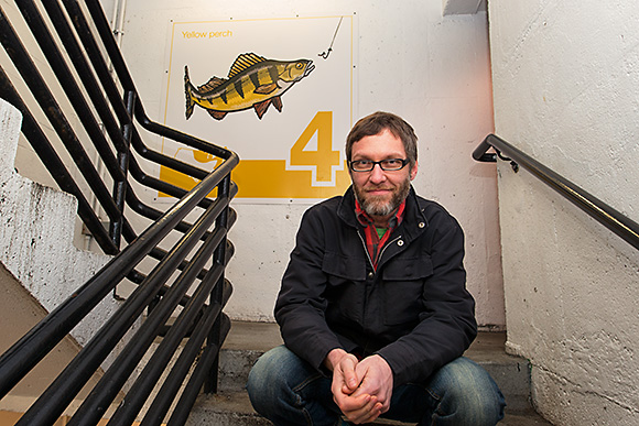 Bruce Worden with one of his art panels at the Maynard Parking Structure in Ann Arbor