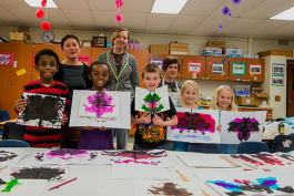 L to R back row Linette Lao, Allida Warn and Christine Bruxvoort stand with students at Erickson Elementary showing off their finished work