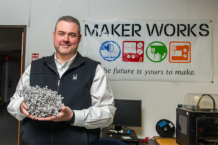 Tom Root with a cast aluminum sculpture at Maker Works