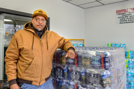 Bryan Foley at Delux Rental with water collected for Flint