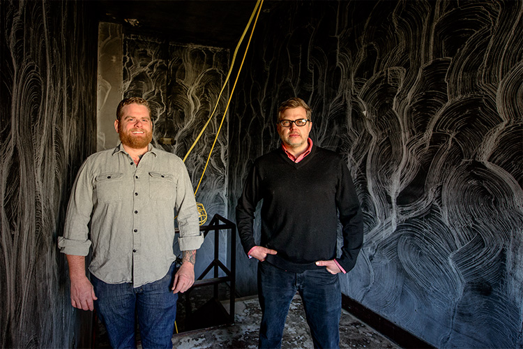 Jesse Kranyak and Mark Maynard in the smoke damaged starewell of Landline Creative Labs