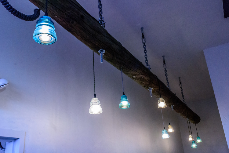 A light fixture at Landline Creative Labs constructed from a telephone pole and glass telephone line insulators.