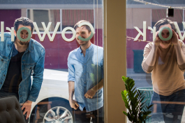 GoWork founders Kyle Thibaut, Andrew Sereno, and Clayton Smith peer through the front window of their business.