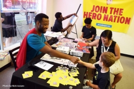 Jermaine Dickerson meets a young attendee at a Hero Nation fundraiser at Go! Ice Cream.