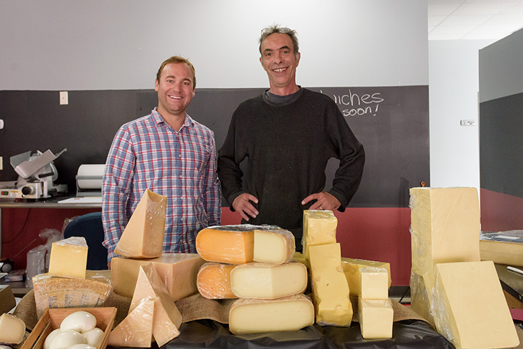 Saline Main Street executive director Riley Hollenbaugh with Cheese Shop of Saline owner John Loomis.
