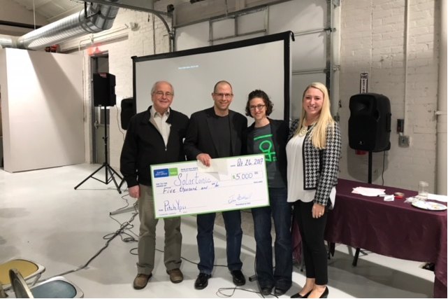 Solartonic cofounders Harry Giles and Brian Tell receive their $5,000 check from Ypsi mayor Amanda Edmonds and Mallory A. Field of Varnum Law.