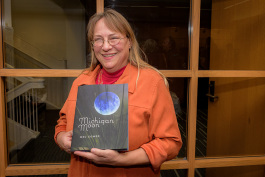"Fifth Avenue Press author Meg Gower with her book ""Michigan Moon."""