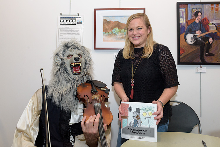 Violin Monster and author Emily Siwek with the picture book A Monster on Main Street