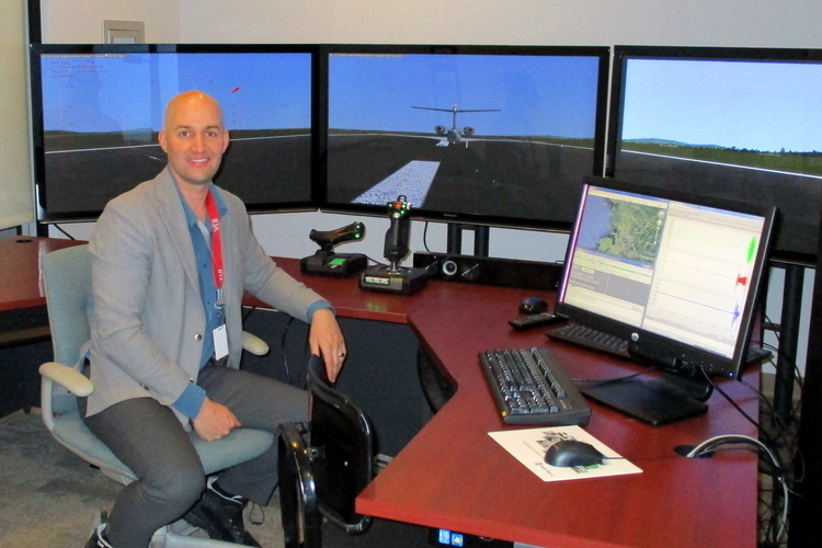 ADI CEO Scott James with ADI's flight simulator behind him.