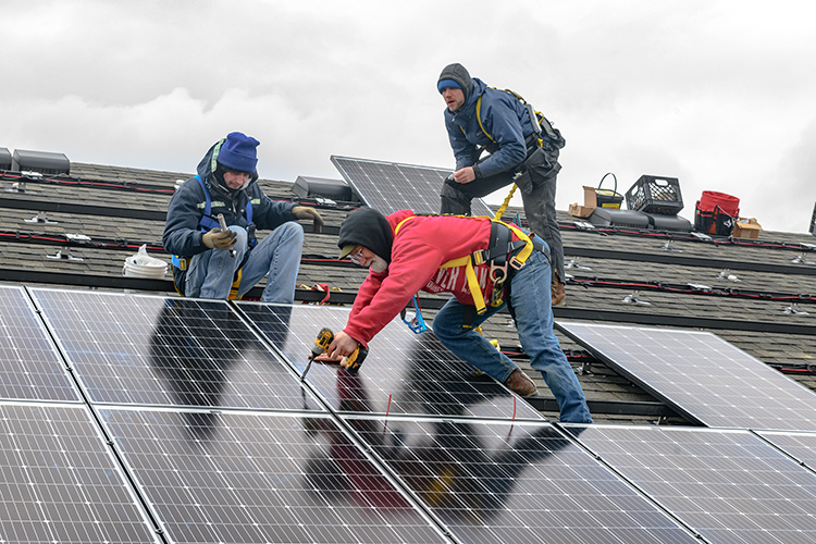 Installing solar panels on the Amos Washington Building at New Parkridge