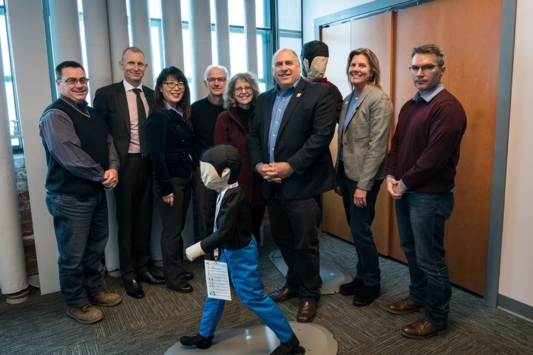 ACM team members pose with a pedestrian test dummy.