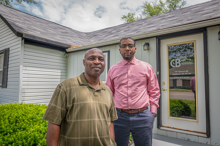 Clyde Montgomery and son Brandan outside of C&B Mortgage Solutions on Ecorse Road