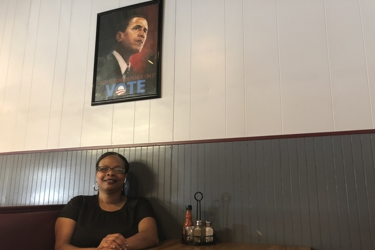 "Andrea ""Cuppy"" White sits in a booth at Cuppy's Best Soulful Cafe."