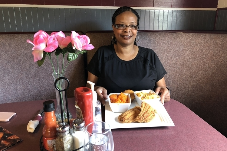 "Andrea ""Cuppy"" White shows off a plate of food at Cuppy's Best Soulful Cafe."