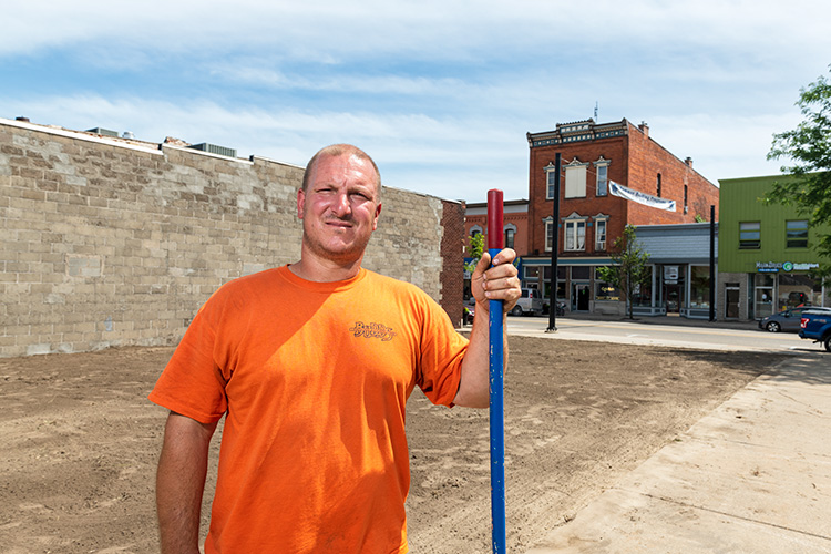 Dan Budd prepares to lay sod for a pocket park at the former Danube Inn site in downtown Milan