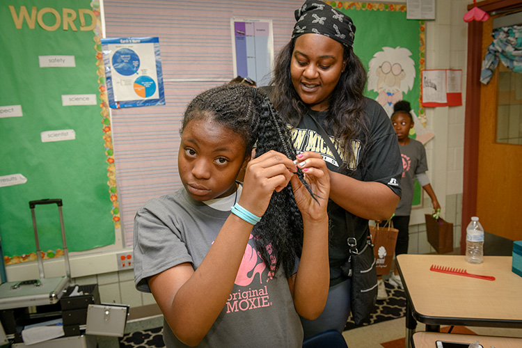Membership/Outreach Specialist for Girl Scouts Heart of Michigan Rola Emauel (R) helps a student at Erickson Elementary with her hair
