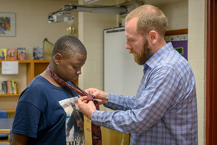 Mosaic Church of Ann Arbor pastor Shannon Nielsen (R) helps a student at Erickson Elementary learn how to tie a tie