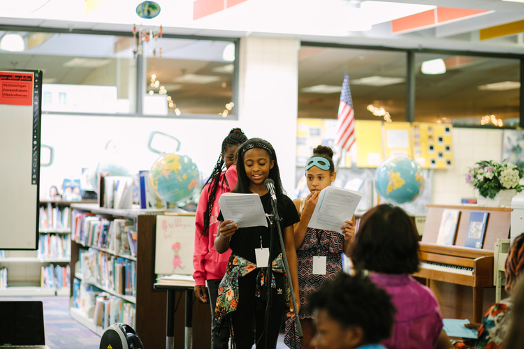 Student writer TaNiyah Lockley speaks at the book release party, as Keymani Barfield and Lilo Gatzke look on.