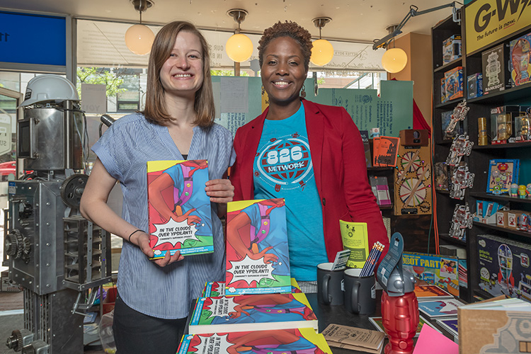 Megan Gilson and Naimah Wade with copies of In The Clounds Over Ypsilanti: Community Superhero Stories