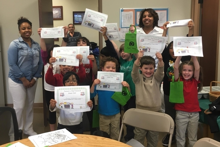 Young participants in Joyful Treats' Cooking Academy hold up their graduation certificates.