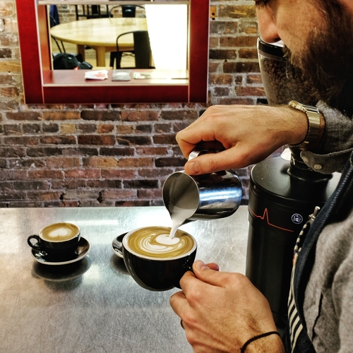 A barista pours a latte at Mighty Good Coffee.