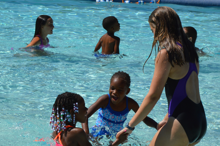 A junior lifeguard teaches girls to swim at Rutherford Pool.