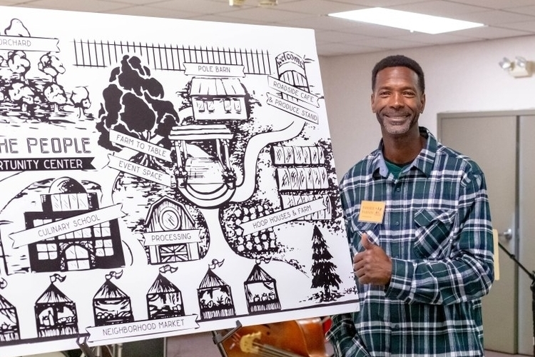 Melvin Parson shows off a concept drawing of We the People Opportunity Center.