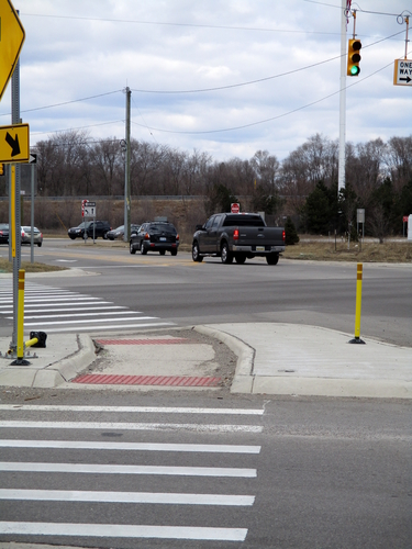 The intersection of Michigan and Dorset Avenues. A knocked-over barrier is visible in the pedestrian island.