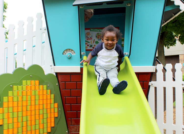 A child uses the slide at the new playscape.