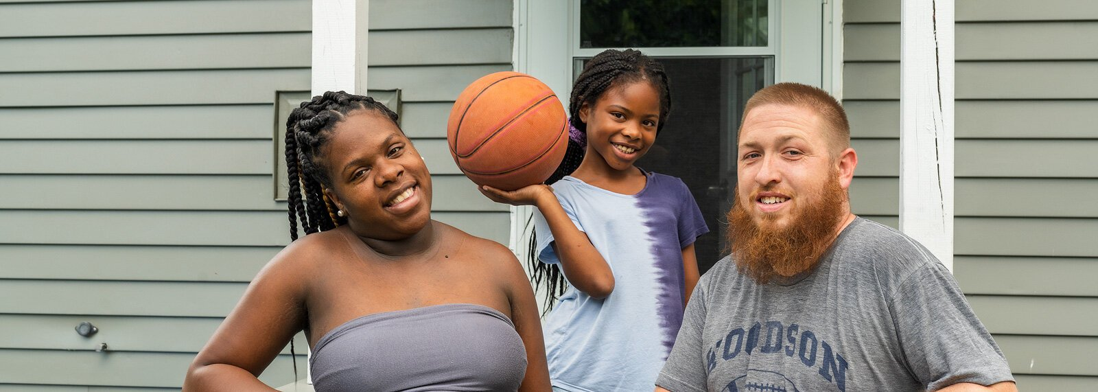 Adriya Perry, her daughter Akavayia, and husband Phil outside their new home in Ypsilanti Township.