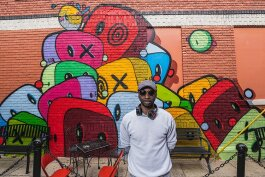 Gary Horton in front of his mural at Go! Ice Cream in Ypsilanti.