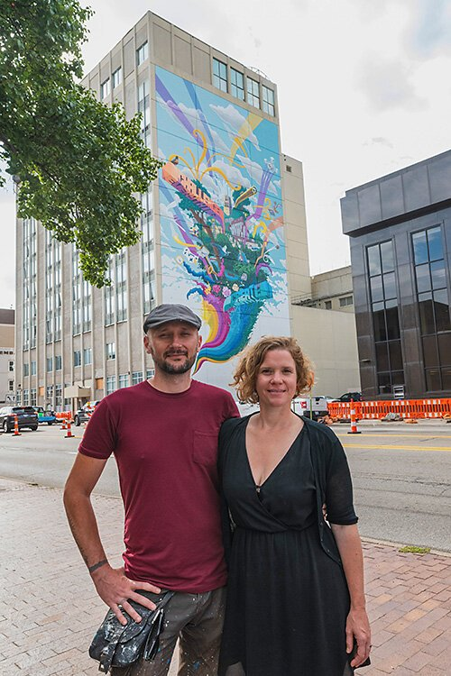 Danijel Matanic and Mary Thiefels of TreeTown Murals in front of their mural at Courthouse Square.