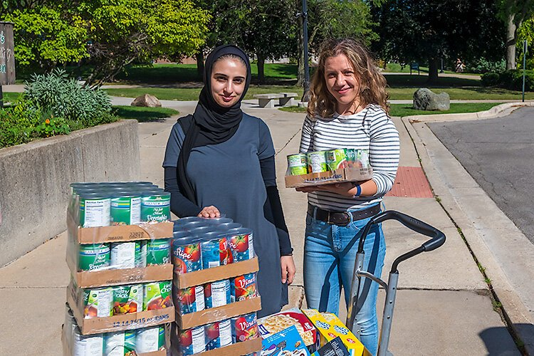 Sara Ajeen and Eliza Caughey unloading food for Swoop's Pantry at EMU.