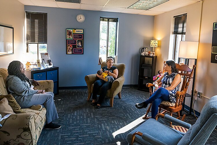 Dera Williams, Najma Treadwell with son Jahleel, and Gayathri Akella at the breastfeeding lounge at the Washtenaw County WIC office.