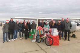 EMU volunteers with one of the planes they used to deliver presents for Operation Good Cheer.
