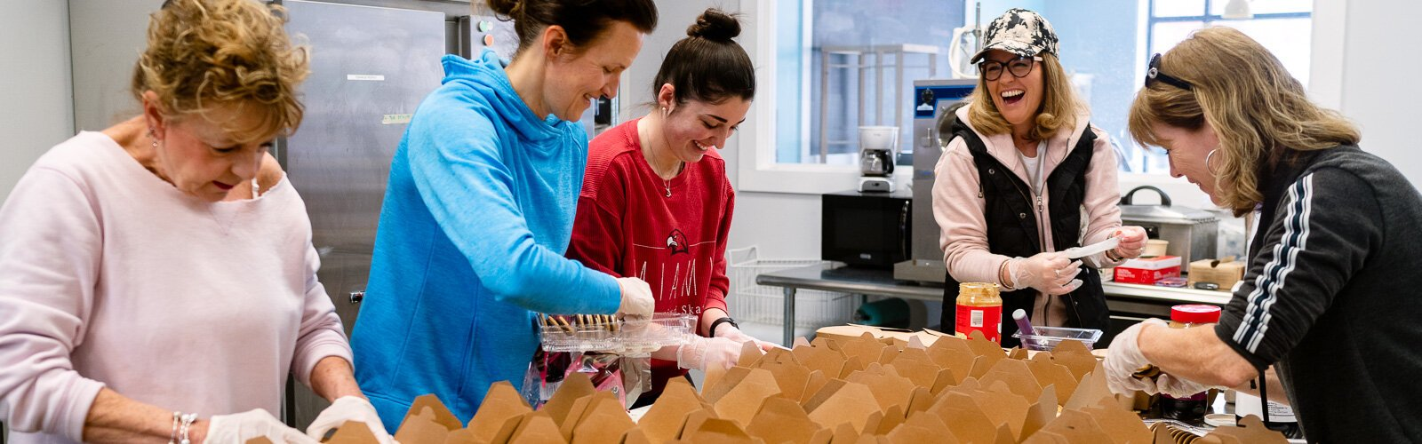 Workers prepare school lunches at Eat More Tea.