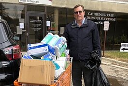 Michael Williams, director of the EMU School of Nursing, stands with items collected for donation to St. Joseph Mercy Health System.