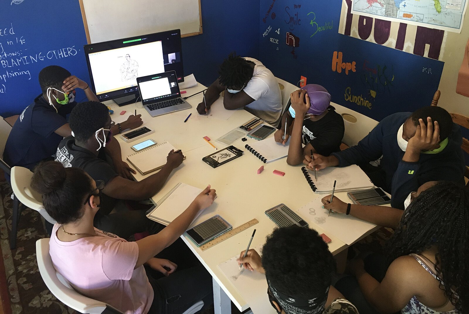 Young people participate in an art class at Educate Youth's clubhouse.
