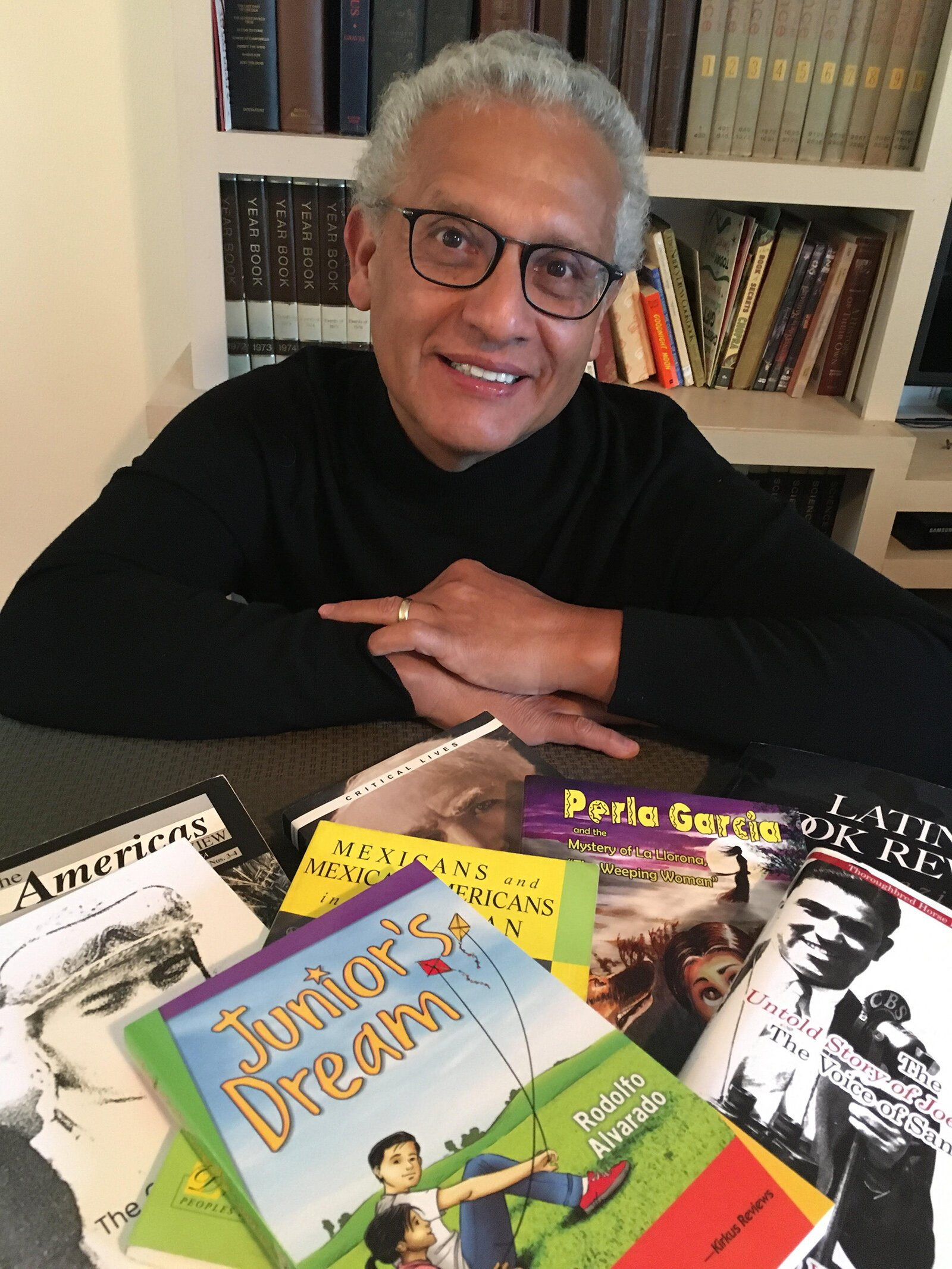 Rodolfo Alvarado with some of the books he's written.