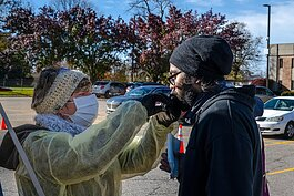 A nasal flu vaccine is administered in the Washtenaw County Health Department parking lot in Ypsilanti.